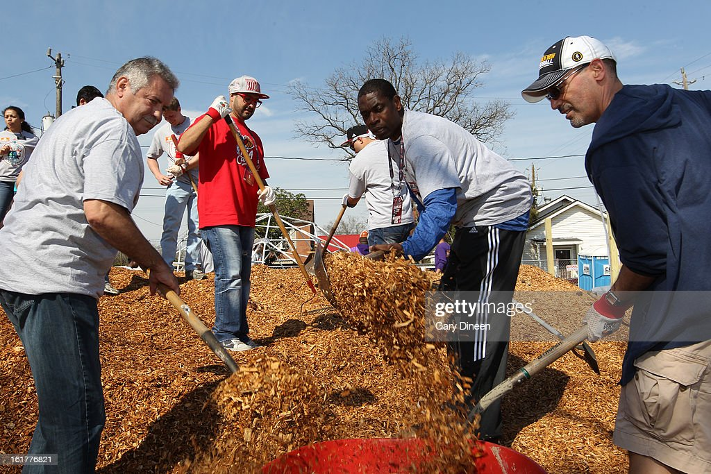 NBA Legend Dikembe Mutombo places mulch in a wheelbarrow at the 2013 NBA Cares Day of Service at the Playground Build with KaBOOM! on February 15, 2013 in Houston, Texas.