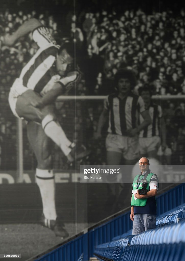Legend West Bromwich photographer Lawrie Rampling stands infront of his picture of West Brom striker Cyrile Regis taken in an 5th Round FA Cup match against Norwich City in February 1982 before the Premier League match between West Bromwich Albion and Middlesbrough at The Hawthorns on August 28, 2016 in West Bromwich, England.