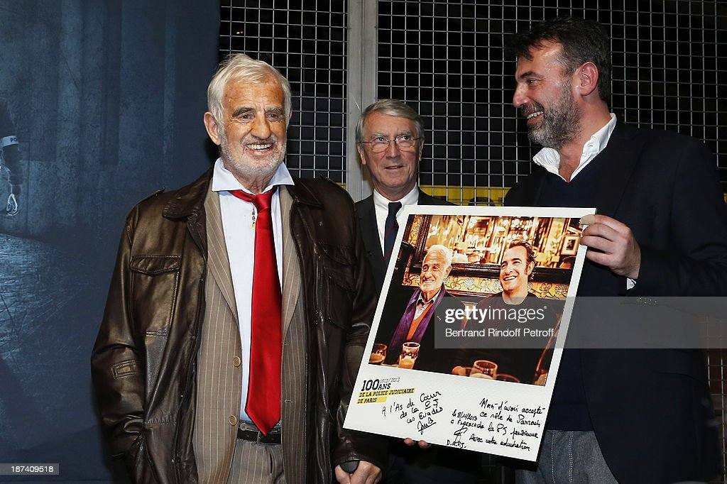 Legendary actor <a gi-track='captionPersonalityLinkClicked' href=/galleries/search?phrase=Jean-Paul+Belmondo&family=editorial&specificpeople=207029 ng-click='$event.stopPropagation()'>Jean-Paul Belmondo</a> (L) is being presented with a photo of him taken with Oscar-winning actor Jean Dujardin on his 40th irthday, during the '100th Anniversary Of The Paris Judiciary Police' exhibition opening on November 8, 2013 in Paris, France. The inscriptions on the photo read : 'Thank you for having accepted this role of patron of the Judicial Police, with our admiration, Christian Flaesch'.