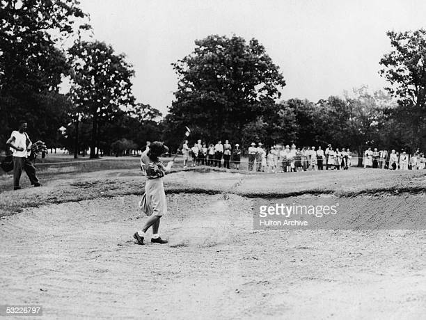 Legendary American athlete Babe Didrikson Zaharias stands in a sand trap on the sixth hole of a golf field and swings out as a crowd of spectators...