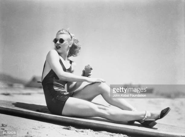 Legendary American dancer and actress Ginger Rogers rubs sun lotion onto her legs before a stint of sunbathing
