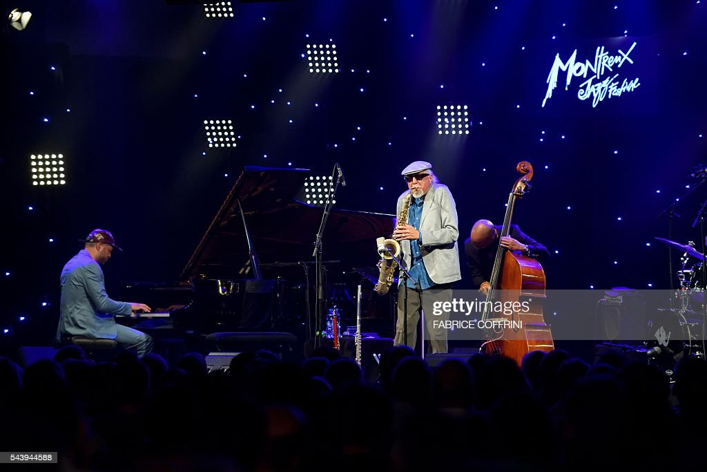 Legendary American jazz musician Charles Lloyd (C) who headlined the first festival in Montreux in 1967 performs on stage at the opening of the 50 edition of the Montreux Jazz Festival on June 30, 2016 in Montreux. Two of the world's greatest jazz musicians opened the star-studded 50th edition of the Montreux Jazz Festival on Thursday, with big names such as Neil Young and PJ Harvey also set to perform at this year's anniversary event. / AFP / FABRICE