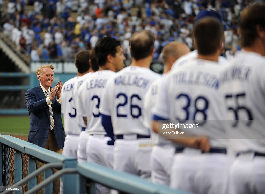 Legendary Dodger Broadcaster Vin Scully stands with players after throwing out ceremonial first pitch at Dodger Stadium on August 30 2012 in Los...