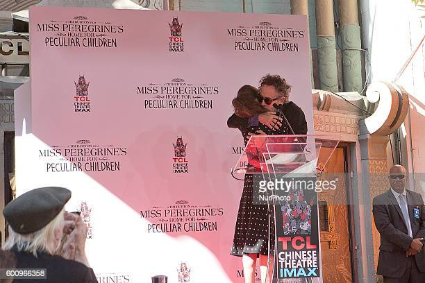 Legendary film director writer and produce Tim Burton hugging two time Oscar nominee and friend Winona Ryder after she introduced him at his Hand and...