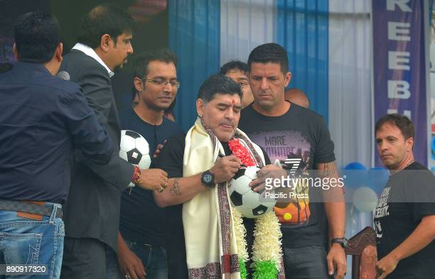 Legendary former footballer of Argentina Diego Maradona signs a football during a presentation at Sreebhumi Sporting Club in Bidhan Nagar He will...