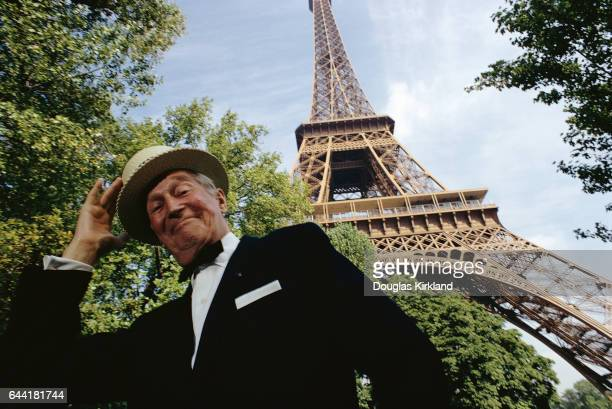 Legendary French singer Maurice Chevalier poses under the Eiffel Tower