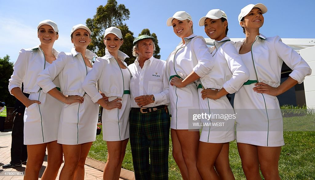 Legendary racing driver Jackie Stewart of Britain (C) poses with promotional models ahead of the Formula One Australian Grand Prix in Melbourne on March 13, 2014. AFP PHOTO / William WEST USE