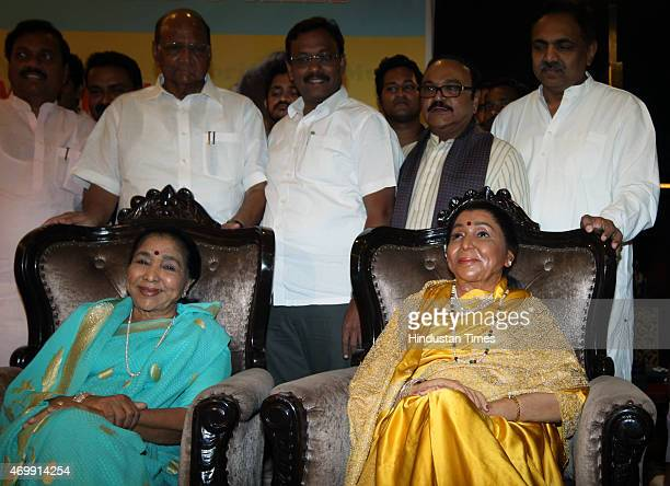legendary singer Asha Bhosle poses with her wax statute as NCP Chief Sharad Pawar looks on during the unveiling of their wax models at the MCA lounge...