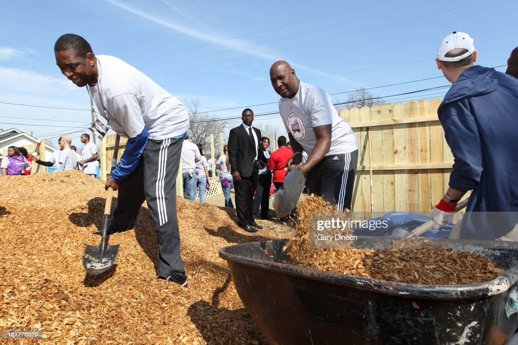NBA Legends Dikembe Mutombo and Darryl Dawkins pick up mulch and place it in a wheelbarrow of the does at the 2013 NBA Cares Day of Service at the Playground Build with KaBOOM! on February 15, 2013 in Houston, Texas.