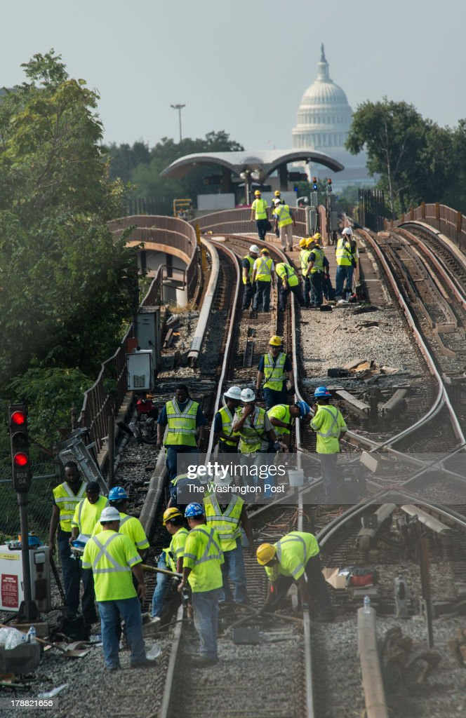 A legion of workers attempt to repair Metro track between the Brookland and Rhode Island Avenue/NoMa-Gallaudet Metro Stations after an overnight derailment, in Washington DC, Friday, August 30, 2013.