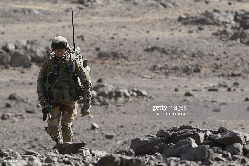 A legionnaire of the French army's 2nd Foreign Parachute Regiment walks during an operation in the Adrar of the Ifoghas mountains on March 17, 2013. A French corporal was killed tracking down jihadist fighters in their northern Mali mountain bastions, bringing to five the number of French deaths since Paris launched a military offensive in the country two months ago. Defence Minister Jean-Yves Le Drian said on March 17, 2013 the 24-year-old soldier was killed and three of his comrades wounded when their vehicle was struck by a roadside bomb blast in the Ifoghas mountains, without saying when it happened. AFP PHOTO / KENZO TRIBOUILLARD AFP PHOTO / KENZO TRIBOUILLARD