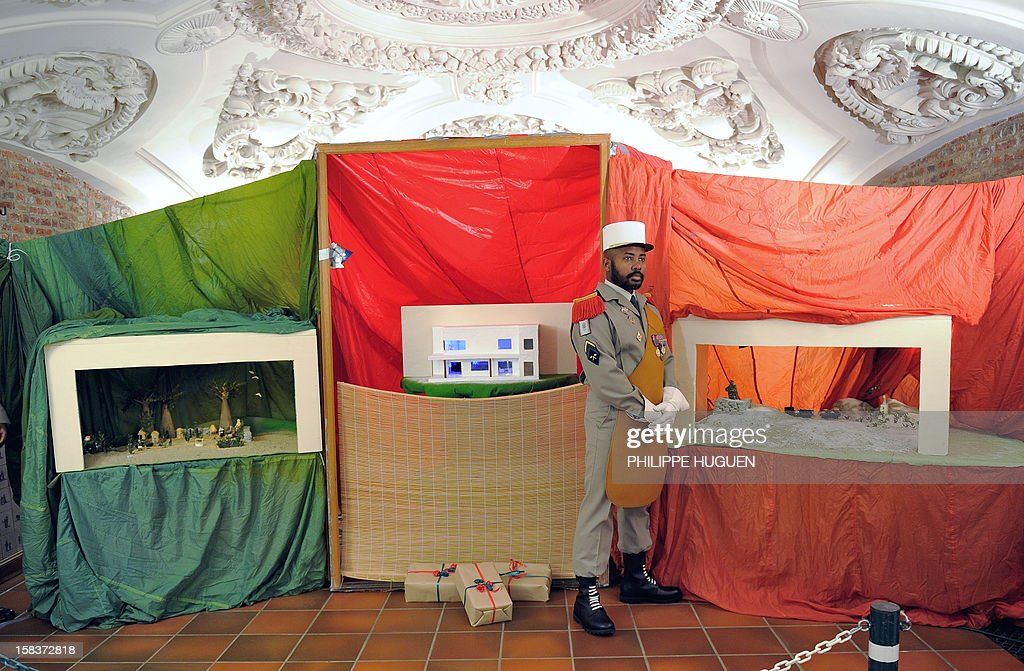 A legionnaire stands between 'Nativity cribs' created by the Foreign Legion, on December 14, 2012, at the Foreign Legion regiment in Lille, northern France. Every Christmas, the Foreign Legion holds a contest of nativity cribs which represent scenes of its military actions throughout the world such as in Afghanistan, Africa.