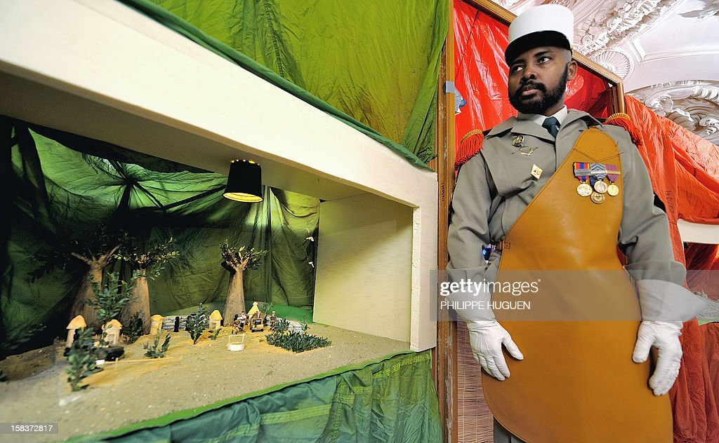 A legionnaire stands next to a 'Nativity crib' created by the Foreign Legion, on December 14, 2012, at the Foreign Legion regiment in Lille, northern France. Every Christmas, the Foreign Legion holds a contest of nativity cribs which represent scenes of its military actions throughout the world such as in Afghanistan, Africa.