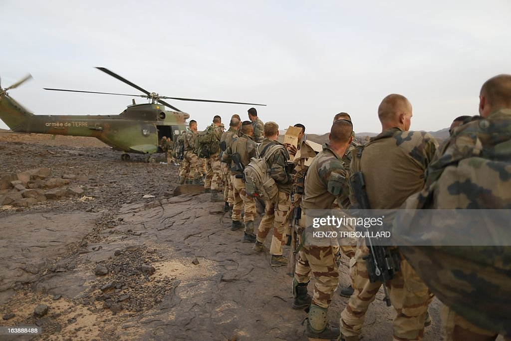 Legionnaires of the French army's 2nd Foreign Parachute Regiment unload a Puma helicopter in the Adrar of the Ifoghas mountains on March 17, 2013. A French corporal was killed tracking down jihadist fighters in their northern Mali mountain bastions, bringing to five the number of French deaths since Paris launched a military offensive in the country two months ago. Defence Minister Jean-Yves Le Drian said on March 17, 2013 the 24-year-old soldier was killed and three of his comrades wounded when their vehicle was struck by a roadside bomb blast in the Ifoghas mountains, without saying when it happened.