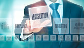 A businessman pressing a Legislation button on a transparent screen.