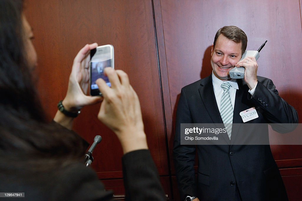 Legislative Counsel Chris Calabrese poses for a photo with a Motorola cell phone from the 1980s -- before a news conference about the 25th anniversary of the Electronic Communications Privacy Act (ECPA) October 18, 2011 in Washington, DC. U.S. Sen. Ron Wyden (D-OR) and U.S. Sen. Mark Kirk (R-IL) called for the ECPA legislation to be updated so to ensure that the government must get a warrant from a judge before tracking our movements or reading our private communications.