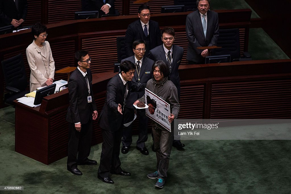 Legislator Leung Kwokhung also known as 'Long Hair' is stopped by the staff of Legislative Council during a protest in front of Chief Secretary...