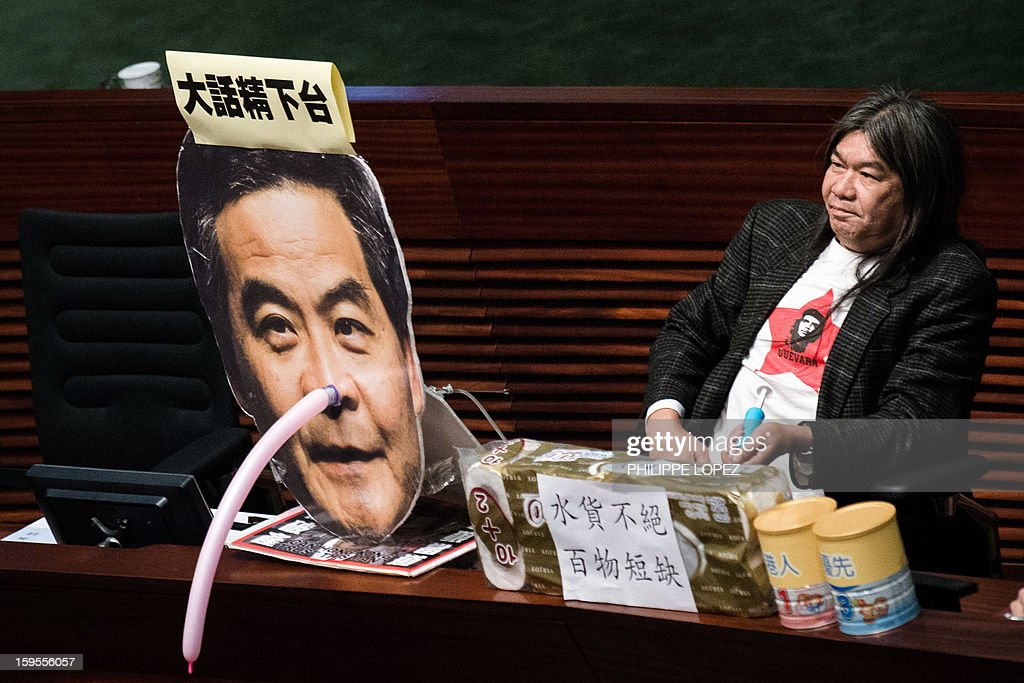 Legislator 'Long Hair' Leung Kwok-hung displays a Pinocchio-style mask over a photo of Hong Kong Chief Executive Leung Chun-ying during his policy address in Hong Kong on January 16, 2013. Leung who won office after he campaigned promising to improve the lives of poor and middle-class citizens, was to give his first policy address amid discontent over issues including sky-high property prices and anti-Beijing sentiment. AFP PHOTO / Philippe Lopez