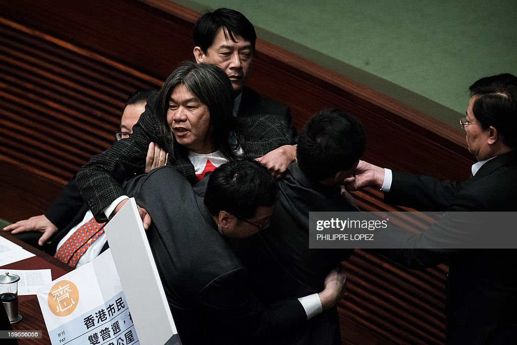 Legislator 'Long Hair' Leung Kwok-hung (L) is escorted out after disrupting the policy address of Hong Kong Chief Executive Leung Chun-ying in Hong Kong on January 16, 2013. Leung who won office after he campaigned promising to improve the lives of poor and middle-class citizens, was to give his first policy address amid discontent over issues including sky-high property prices and anti-Beijing sentiment. AFP PHOTO / Philippe Lopez