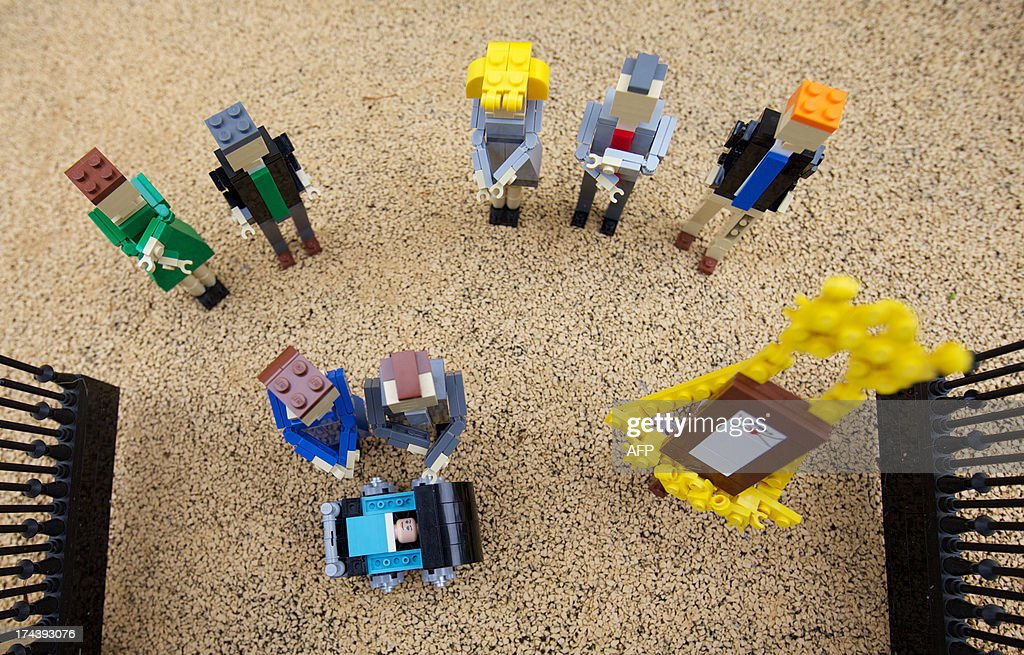 Lego models of Prince William, the Duke of Cambridge and his wife Catherine, The Duchess of Cambridge along with a pram containing a model of their newborn baby boy George Alexander Louis are postitioned outside a 36000 Lego-brick model of Buckingham Palace at Legoland in Windsor on July 25, 2013. Britain's press gave their seal of approval to Prince William and his wife Kate's decision to name their newborn baby boy George Alexander Louis, saying it had 'kingly authority'. AFP PHOTO / ANDREW COWIE
