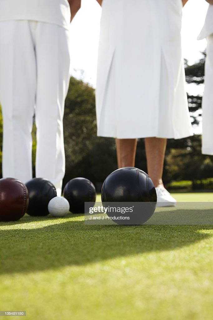 Legs and bowls on a bowling green
