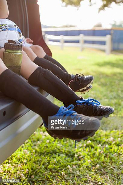 Legs and feet of boy and younger sister sitting in car boot wearing football boots