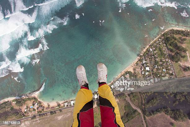 Legs and feet of skydiver above coastline