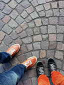 Legs and feet of two people wearing sneakers standing on cobblestone pavement from above with copy space