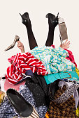 Girl legs and hands reaching out from a big pile of clothes and accesories. Woman buried under an untidy cluttered wardrobe. Woman in high heels needs help from to much shopping. Shopaholic girl.