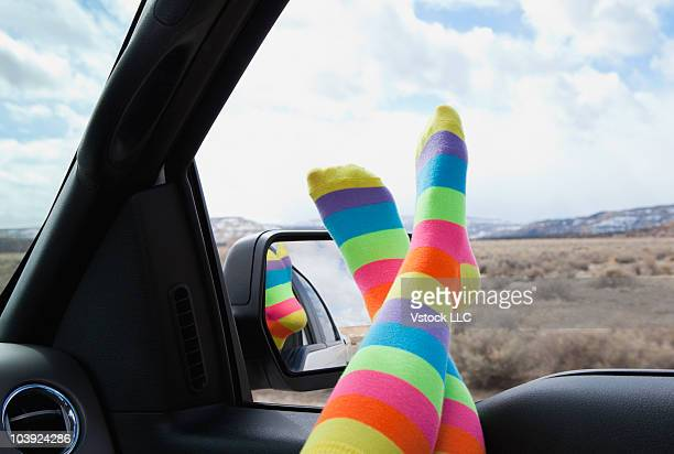 Legs clad in colorful socks hanging out of car window