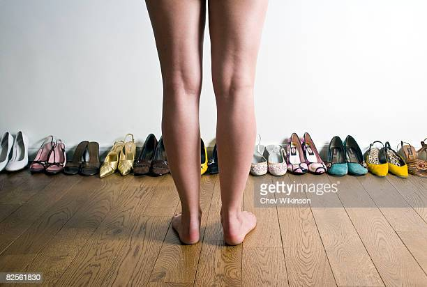 Legs in front of row of shoes