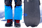 Man standing in snowboarder boots on the top of the alps mountain with snowboard