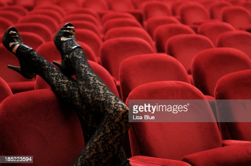 Legs Leaning on Theater Chair