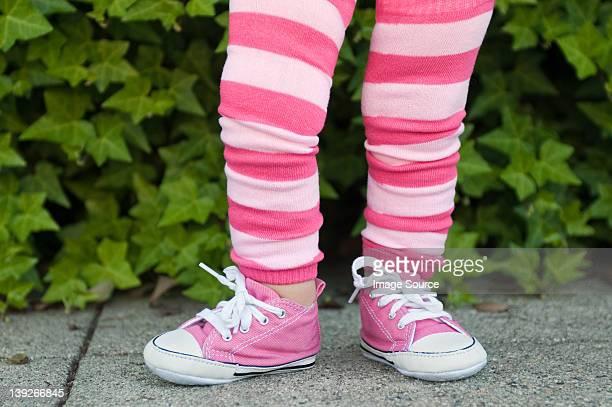 Jambes d'un jeune enfant en rose rayé et leggings