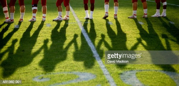 Legs of American football players on field, (Digital Enhancement)