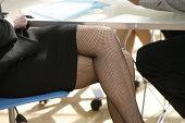 Legs of businesswoman wearing fishnet stockings in meeting