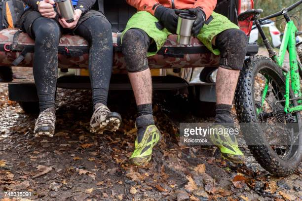 Legs of Caucasian couple sitting in pickup truck near bicycle