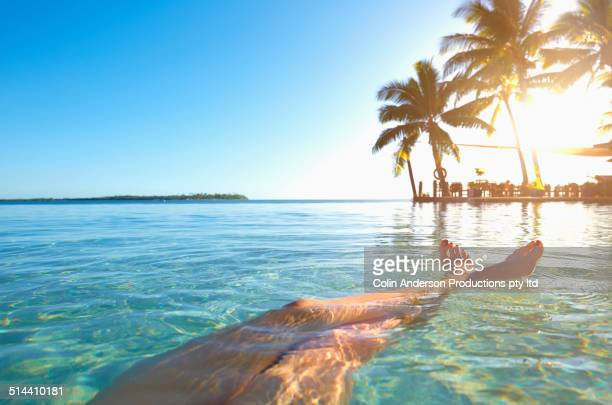 Legs of caucasian girl relaxing in tropical ocean