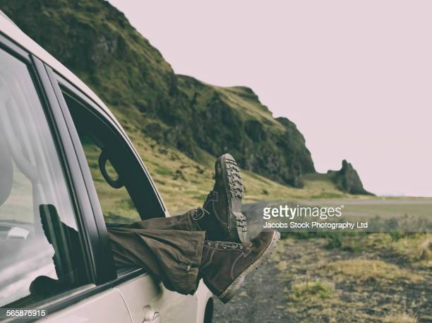 Legs of Caucasian woman dangling from car window on remote road