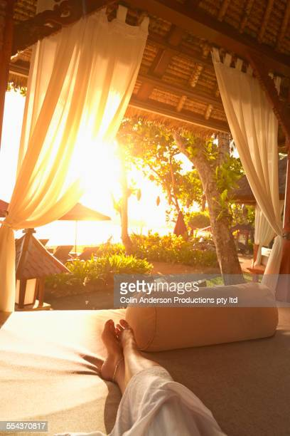 Legs of caucasian woman relaxing in cabana