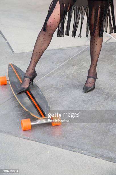 Legs of Caucasian woman wearing high heels on skateboard