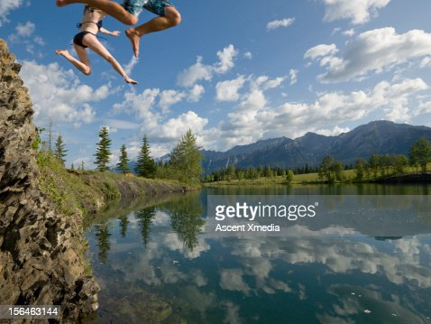 Legs of couple plunging towards a mountain lake : ストックフォト