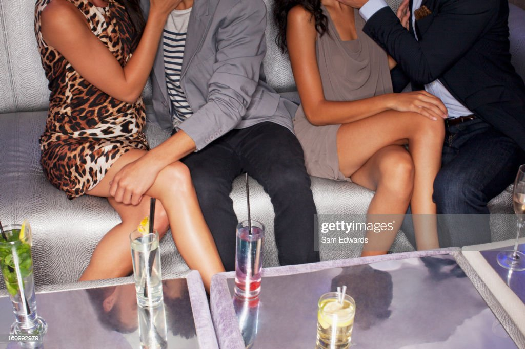 Legs of couples sitting on sofa in nightclub : Stock Photo