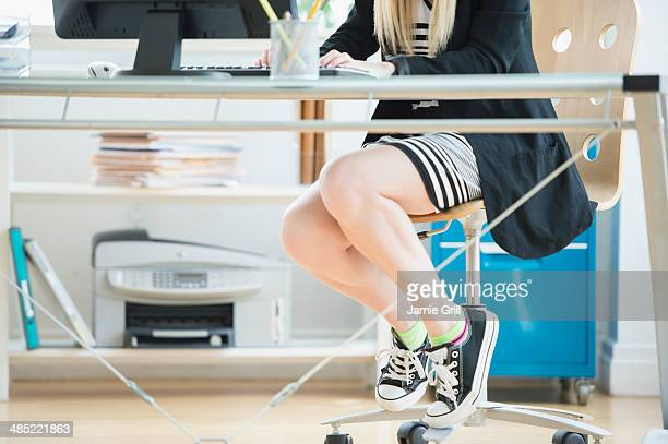 Legs of female designer sitting at desk