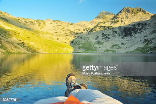 Legs of female hiker by mountain lake, Bulgaria