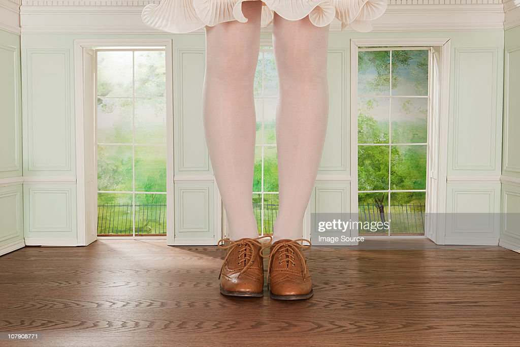 Legs of giant woman in tiny room