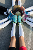 Vertical image of young female players of handball sitting on court with stretched legs and ball in the middle.
