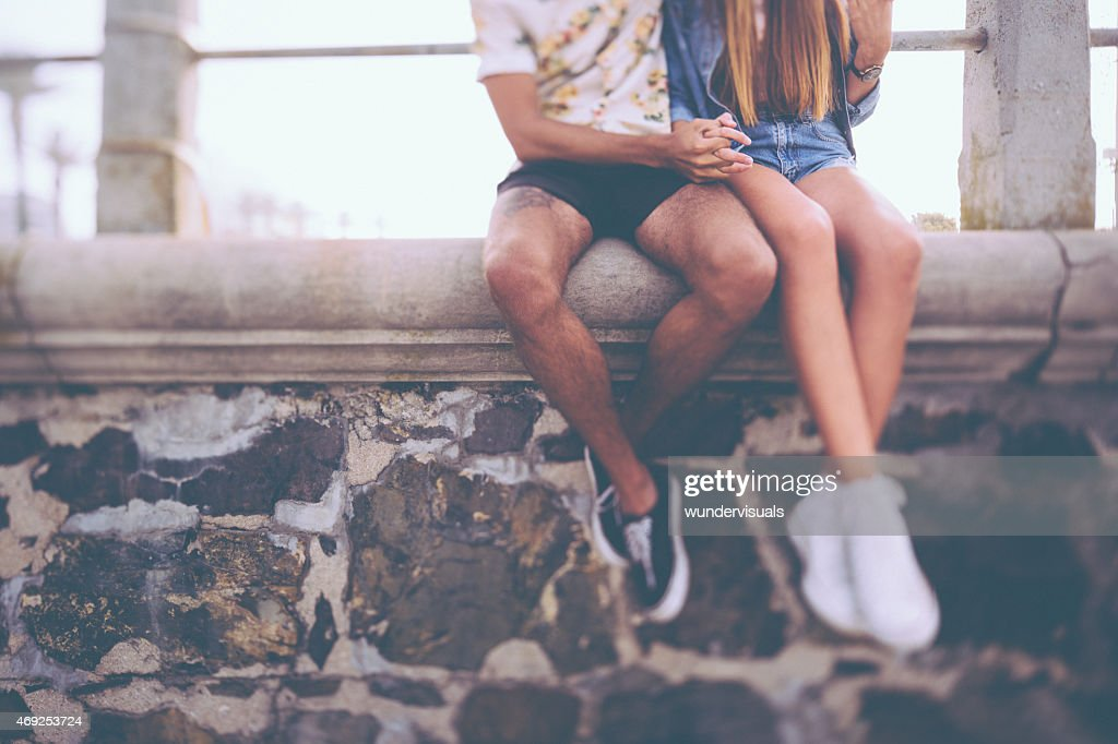Legs of hipster couple sitting on a wall holding hands : Stock Photo