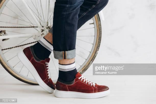 Legs of man standing near bicycle wheel