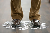 Legs of Man Standing on Torn Paper